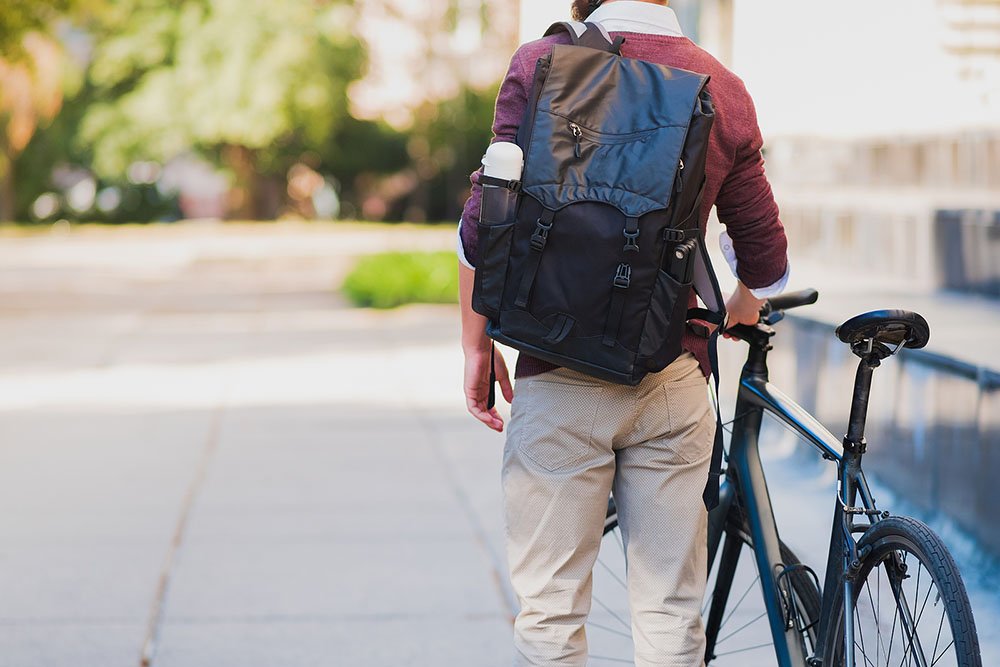 Male Commuter Or Messenger With A Bike In Urban Background. Safe
