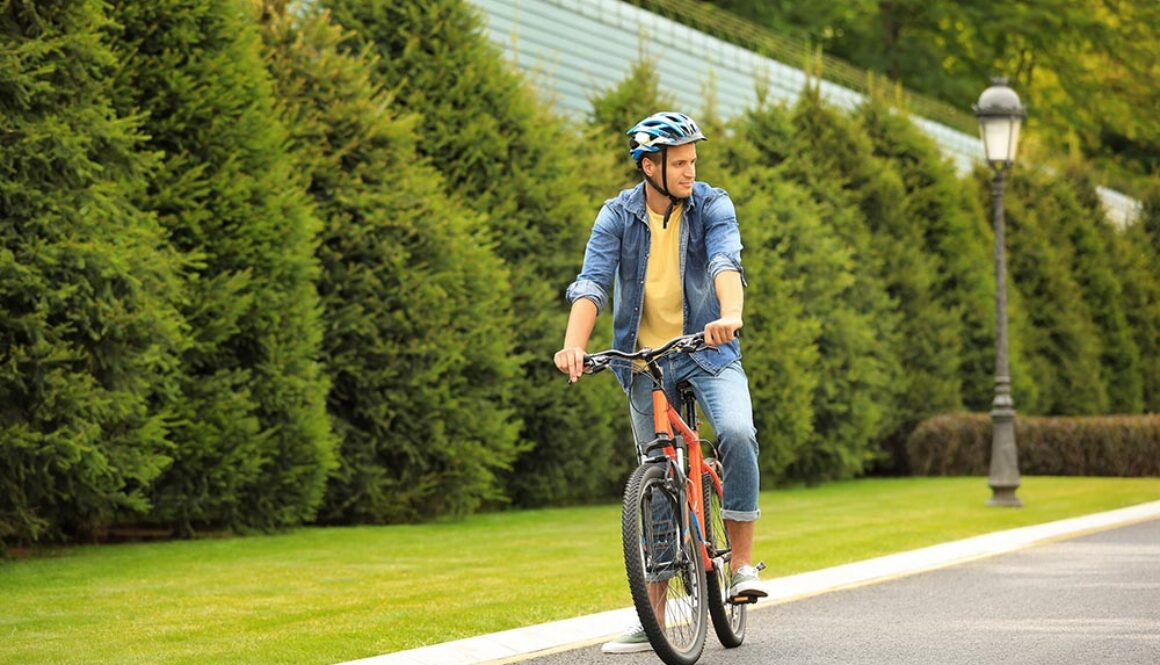Young Man In Helmet Riding Bike Outdoors